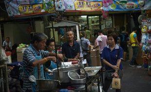 Un vendeur prépare à manger dans une allée du quartier chinois de Bangkok, le 12 avril 2016