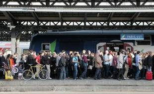 Des usagers de la SNCF attendent un train sur un quai de la gare de l'Est, le 11 juin 2014 à Paris