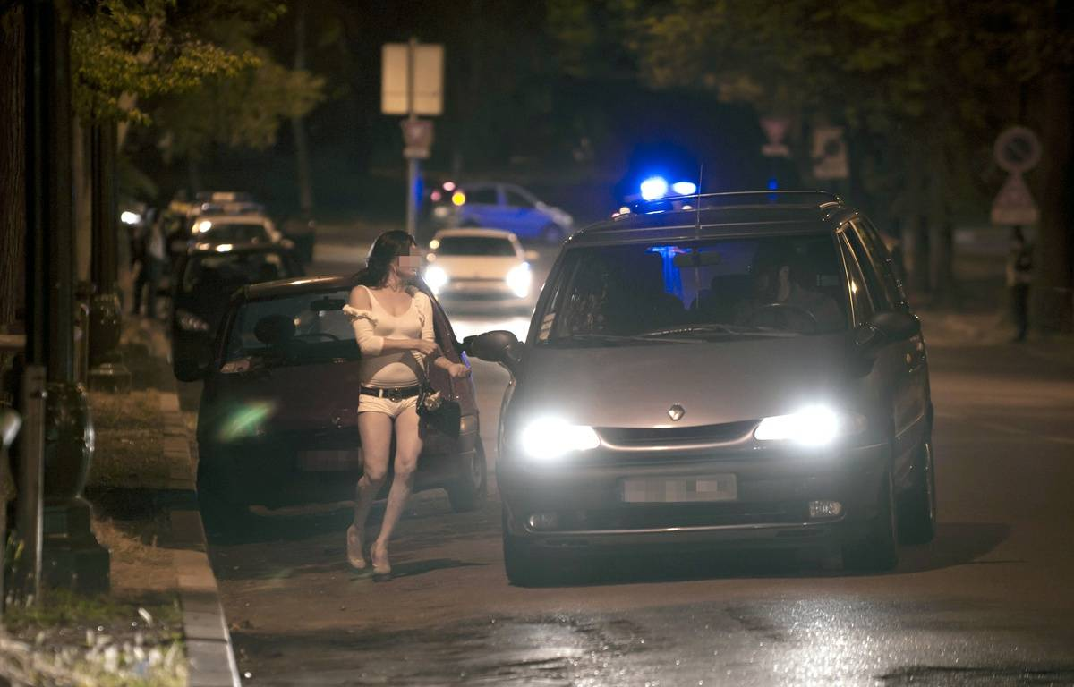 Une prostituée parle avec le chauffeur d'une