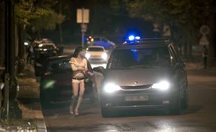 Paris, le 6 juin 2011. Une prostituée parle avec le chauffeur d'une voiture aux abords du Bois de Boulogne.