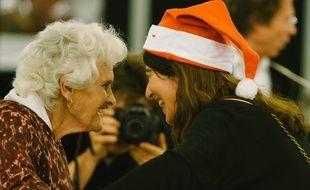 Une bénévole et une participante d'un réveillon de Noël organisé par Les petits frères des pauvres.
