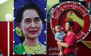 Un homme et un bébé passent devant une affiche à l'effigie d'Aung San Suu Kyi, le 8 novembre 2015 à Mandalay, en Birmanie.
