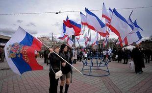 Deux femmes tiennent un drapeau russe (G) sur la place Lenine à Simferopol le 16 mars 2014