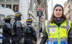 Les membres de l'Observatoire des pratiques policières portent des chasubles jaune et bleu lors des manifestations.