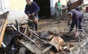 Des habitants de Rasiguères (Pyrénées-Orientales) nettoient leurs maisons après des inondations, le 1er décembre 2014