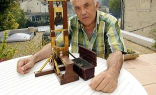 A file picture taken on September 20, 2002, shows France's last surviving executioner in Algeria Fernand Meyssonnier showing the miniature replica of a guillotine in Fontaine-de-Vaucluse, southern France. He made this replica at the age of 15 as a present for his father who was chief executioner and inducted his son as an apprentice in 1947. AFP PHOTO GERARD JULIEN