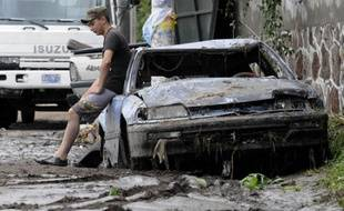 Un habitant du Salvador sur sa voiture détruite par les coulées de boue, le 8 novembre 2009.