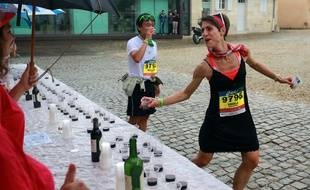 Une concurrente s'arrête boire un petit verre de vin pendant la course.