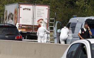 Forensic officers stand in front of a truck inside which were found a large number of dead migrants on a motorway near Neusiedl am See, Austria, on August 27, 2015. The vehicle, which contained between 20 and 50 bodies, was found on a parking strip off the highway in Burgenland state, police spokesman Hans Peter Doskozil said at a  press conference with Interior Minister Johanna Mikl-Leitner. AFP PHOTO / DIETER NAGL