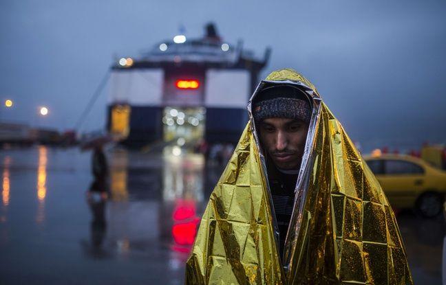 Un migrant enveloppé dans une couverture de survie attend d'embarquer à bord d'un ferry dans le port du Pirée, près d'Athènes, le 5 janvier 2016.