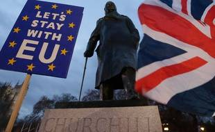 (190115) -- LONDON, Jan. 15, 2019 (Xinhua) -- Protesters hold a flag and a placard outside the Houses of Parliament, in front of a statue of Winston Churchill, in London, Britain on Jan. 15. 2019. The British parliament on Tuesday rejected overwhelmingly the Brexit deal, further complicating the country's historic exit from the European Union (EU).