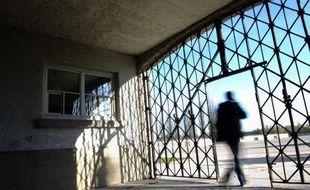 """Un visiteur emprunte le portail d'entrée de l'ancien camp de concentration de Dachau en Allemagne dont la porte qui portait le slogan nazi """"Arbeit macht frei"""" (le travail rend libre) a été dérobée, le 3 novembre 2014"""
