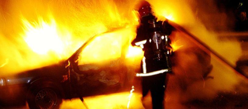 Un pompier intervient sur un incendie de voiture. Illustration.