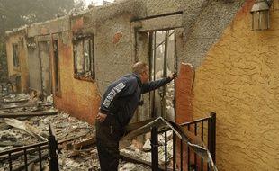 Un habitant inspecte la maison de son voisin, ravagée par les flammes à Paradise, en Californie, le 10 novembre 2018.