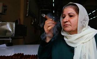 L'employée Oum Ali fume un cigare produit dans la première usine syrienne de fabrication de cigares, la Compagnie générale du tabac le 17 mars 2015