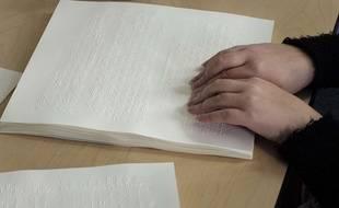 Une personne handicapée déchiffre une feuille de braille.