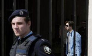 Un policier grec sécurise l'entrée de l'établissement athénien dans et devant lequel a eu lieu la fusillade.