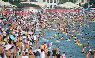 Des vacanciers se rafraichissent au bord d'une plage de Qingdao, à l'est du pays.