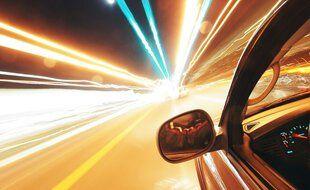 Une voiture roulant à vive allure sur une route (illustration).