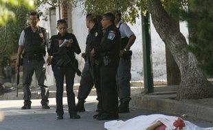 Des policiers fédérals méxicains enquêtent près du corps d'une femme assassinée avec son petit-ami à Ciudad Juarez le 5 juillet 2010.