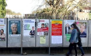 Des passants marchent devant les panneaux d'affichage des candidats aux élections municipales à Rennes, le 12 mars 2020.
