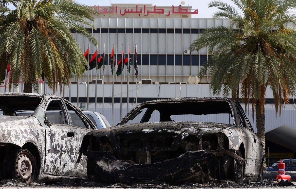 Des véhicules calcinés devant l'aéroport international de Tripoli, en Libye, le 14 juillet 2014, après l'attaque menée par des milices islamistes. – AFP