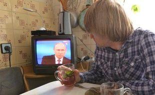 Un habitant de Stavropol regarde le président russe Vladimir Poutine tenir à Moscou, le 16 avril 2015, sa séance annuelle de questions-réponses en direct à la télévision