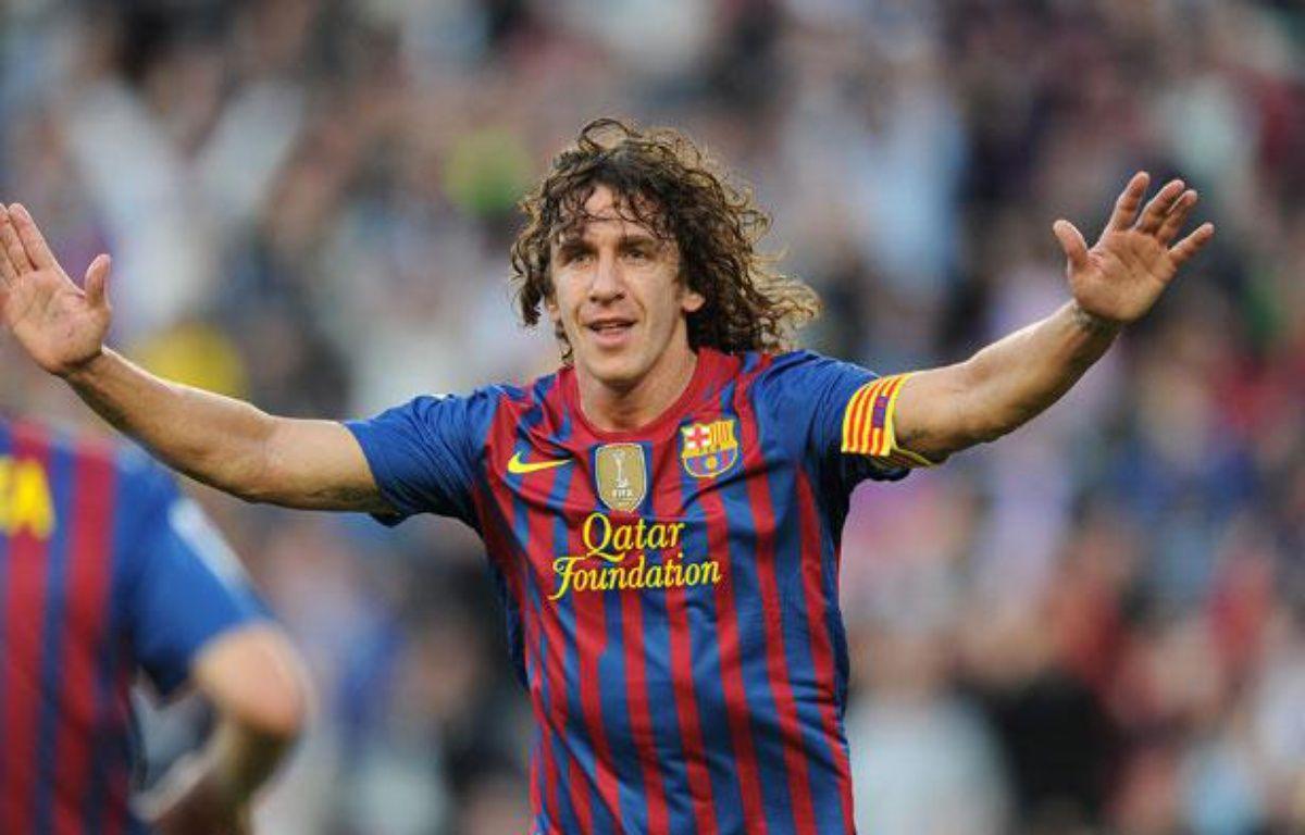Carles Puyol le 3 mai 2012, montre sa joie après avoir marqué un but contre Malaga au Camp Nou. – LLUIS GENE / AFP