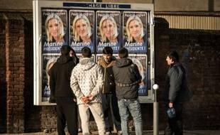 Des migrants regardent les panneaux électoraux à Calais avec en affiche la tête de liste FN de la région Nord, Marine Le Pen, le 7 décembre 2015