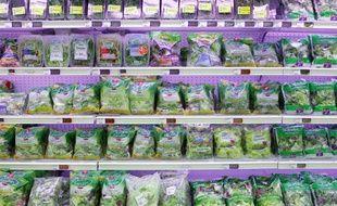 Des sachets de salade sur les rayons d'un supermarché.