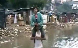 Un journaliste indien, qui faisait un reportage sur des inondations, apparait juché sur les épaules d'un rescapé