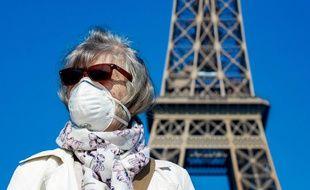 Une femme porte un masque devant la Tour Eiffel, à Paris le 12 avril 2020.