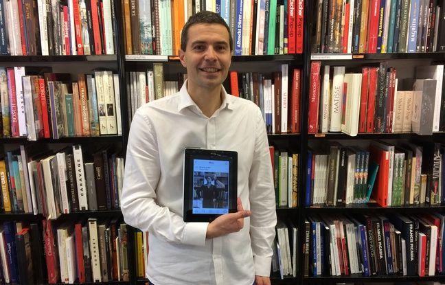 David Pigeret, libraire responsable du rayon Beaux-Arts, tient l'ipad avec lequel il photographie les