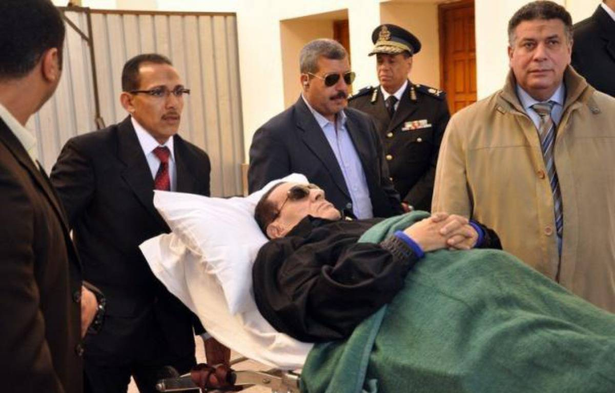 Ousted Egyptian President Hosni Mubarak is wheeled on a stretcher out of the police academy after his murder trial in Cairo on January 10, 2012. AFP PHOTO / STR – - afp.com