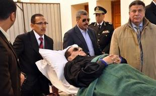 Ousted Egyptian President Hosni Mubarak is wheeled on a stretcher out of the police academy after his murder trial in Cairo on January 10, 2012. AFP PHOTO / STR