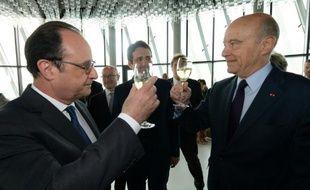 Le maire de Bordeaux  Alain Juppé (d) et le président François Hollande trinquent le 31 mai 2016, lors de l'inauguration de la Cité du Vin à Bordeaux