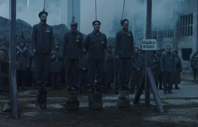 Un panneau «Photographies interdites» à côté de prisonniers de camps de concentration sur le point d'être exécutés.
