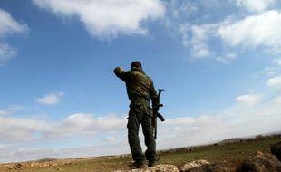 Un soldat syrien regarde en direction de la ville de Daraa depuis sa position à Soueida, dans le sud de la Syrie, le 23 janvier 2013