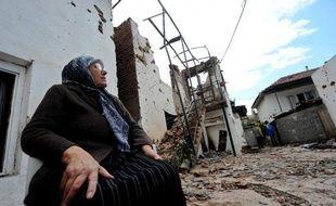 Une femme est assise à l'extérieur de sa maison en ruine, le 11 mai 2015 à Kumanovo, dans le nord de la Macédoine