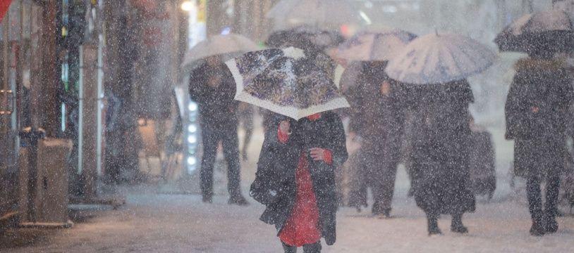 Des passants sous la neige dans une rue de Shinjuku, à Tokyo, le 22 janvier 2018.