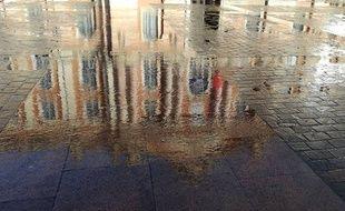 Le reflet de la façade du Capitole dans une flaque d'eau.