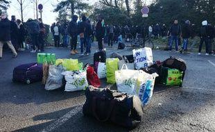 Les migrants expulsés ont rassemblé leurs affaires sur un parking.
