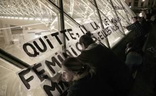 Des manifestants posent des pancartes sur la pyramide du Louvre lors d'une manifestation pour dénoncer les féminicides et les violences conjugales, le 14 septembre 2019 à Paris.