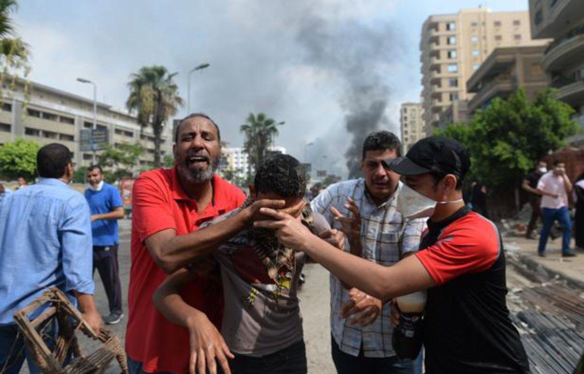 Au Caire, des partisans de Morsi fuient les gaz lacrymogènes, le 14 août 2013. – AFP PHOTO / KHALED DESOUKI