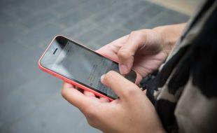 Jeune femme envoyant un sms avec un téléphone portable. Illustration.