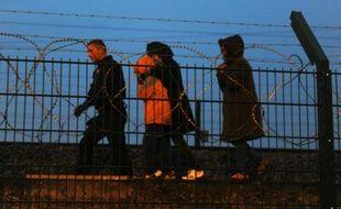 Des policiers arrêtent des migrants sur le site de Eurotunnel à la gare de Calais, le 13 août 2015