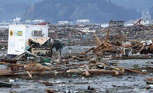 Un homme fouille les ruines à la recherche de souvenirs de sa femme disparue dans le séisme, le 13 mars 2011 à Rikuzentakada, dans le nord du Japon.