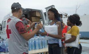 Un membre de la Croix-Rouge distribue de l'eau à des sinistrésn le 21 septembre 2017 à Saint-Martin. AFP PHOTO / Helene Valenzuela