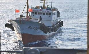 Un marin chinois utilise un long crochet pour tenter de s'accrocher à un câble déployé par un navire américain en mer de Chine méridionale