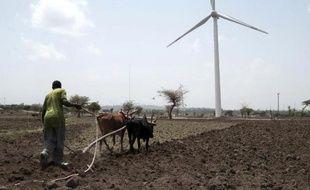 Un agriculteur éthiopien laboure son champ au pied d'une éolienne sur les hauteurs d'Adama, au sud d'Addis Abeba, le 15 juin 2015
